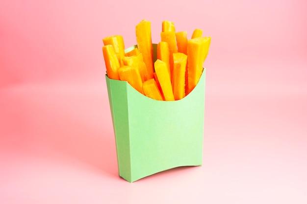 新鮮なニンジンはピンクの背景に緑の紙箱にスナックを貼り付けます