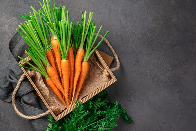 Fresh carrots in a wooden box on a brown background. top view, copy space. natural, fresh products. Premium Photo
