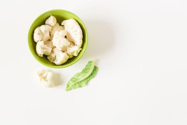 Свежая цветная капуста в зеленой тарелке. белый фон. концепция органических продуктов питания.