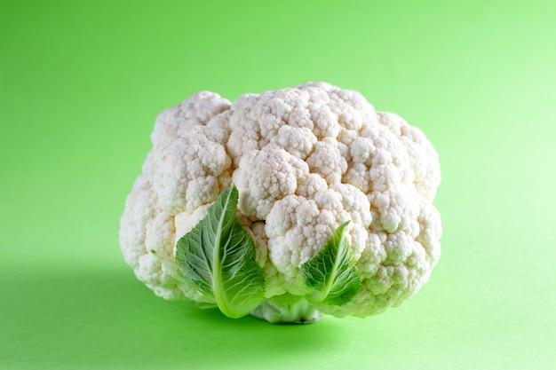 色の背景に新鮮なカリフラワー。季節の野菜ミニマルスタイル。最小限のスタイルの料理。