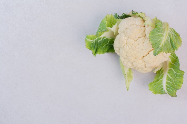 Свежая цветная капуста с листьями на белой поверхности