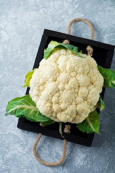 Fresh cauliflower in a wooden box on a light table. selective focus.top view.copy space.