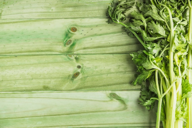 Fresh celery on green wooden plank