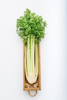 Fresh celery in wooden tray on white backdrop