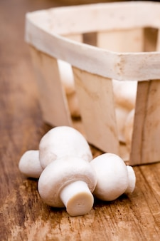 Fresh champignon and a basket on wooden background