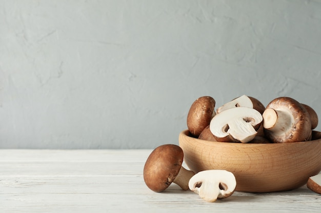 Fresh champignon mushrooms in bowl on white wood, space for text