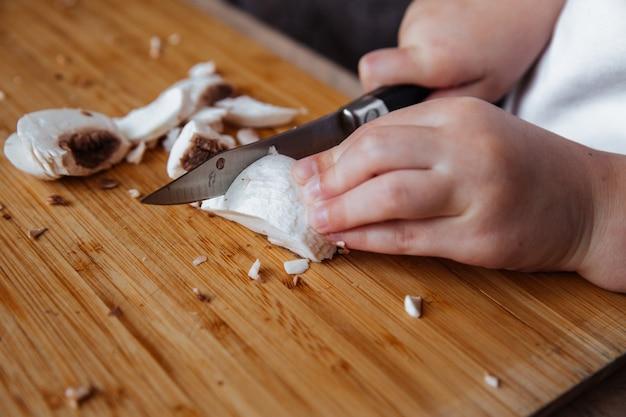 木の板の女の子の新鮮なシャンピニオンキノコはナイフでキノコをカットします
