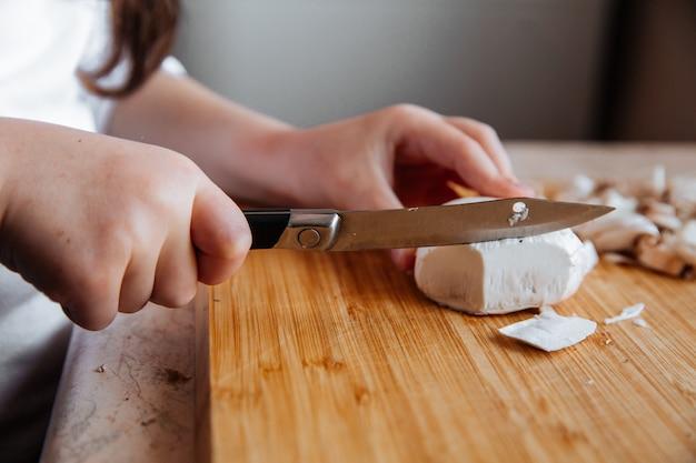 木の板に新鮮なシャンピニオンのキノコ、女の子はナイフでキノコをカットします。