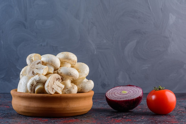 Fresh champignon mushrooms with red tomato and purple onion on a dark surface
