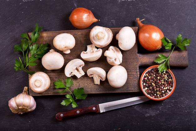 暗いテーブル、上面図に野菜と新鮮なシャンピニオンキノコ