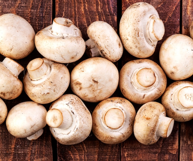 Fresh champignon mushrooms on wooden table, top view. copy space