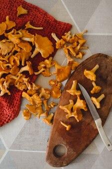 Свежие грибы лисички на деревянной разделочной доске с ножом на кухонном столе