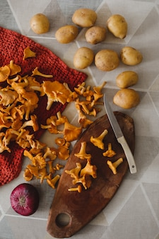 Свежие грибы лисички, картофель и лук на деревянной разделочной доске с ножом на кухонном столе