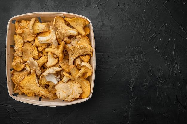 나무 상자 컨테이너에 있는 신선한 살구 버섯 세트, 검은색 짙은 석재 테이블 배경, 위쪽 뷰 플랫 레이, 텍스트 복사 공간