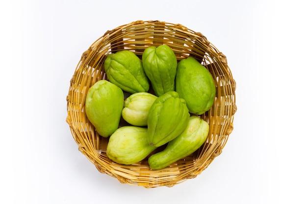 Fresh chayote fruit in bamboo basket on white background.