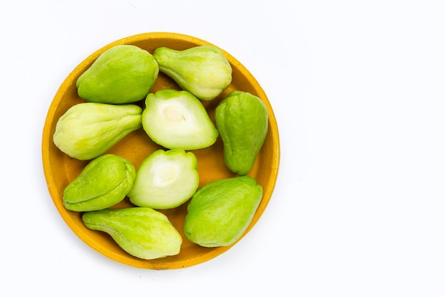 Fresh chayote fruit in yellow plate on white background.