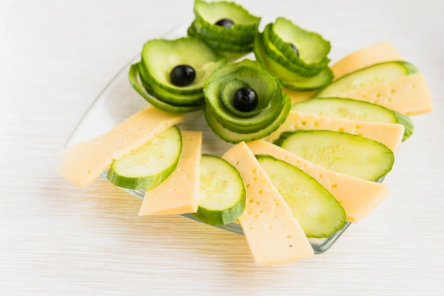 Fresh cheese, cucumber and avocado with olives on dish on table