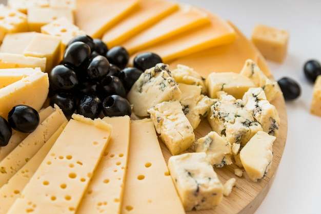 Fresh cheese and olives on chopping board