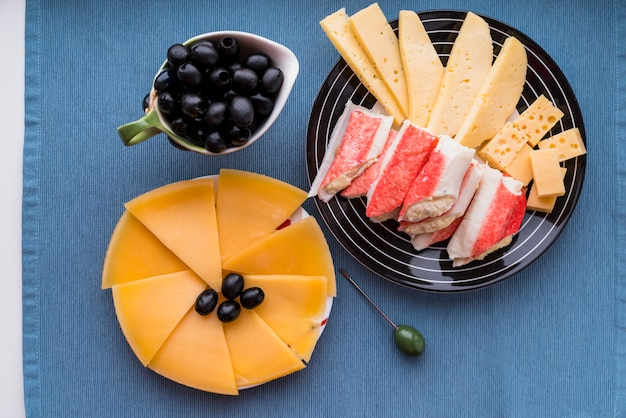 Fresh cheese and snacks near olives on plates