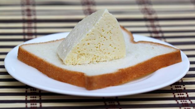 Свежий сыр с хлебом на белой тарелке