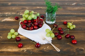 Fresh cherries and grapes in bowl on wooden backdrop