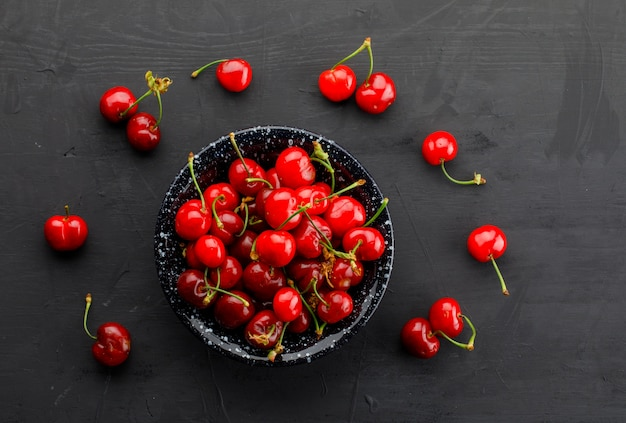 Fresh cherries in a black plate on a dark table. top view.