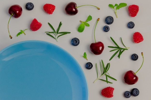 Fresh cherries, blueberries, raspberries, mint and rosemary leaf on top view with blue.