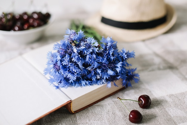 Свежая вишня, васильки, соломенная шляпа и книга на столе, летняя квартира, вид сверху