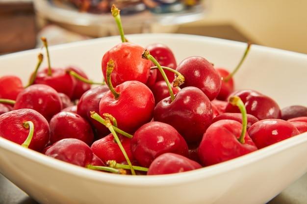 Свежая вишня в белой тарелке, готовая к употреблению.