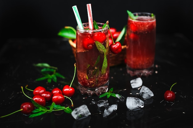Fresh cherries placed in a basket and black cherries with water splashes