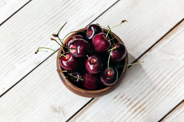 Fresh cherries in a small bowl on a wooden , top view