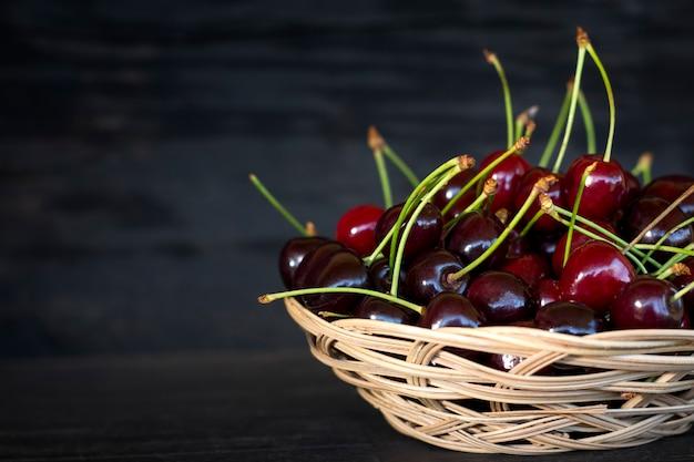 Свежие ягоды вишни в плетеной тарелке на темном деревенском деревянном фоне