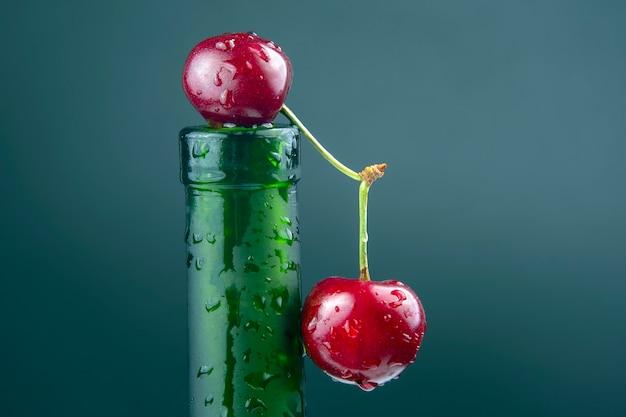 Свежая ягода вишни с каплями воды на зеленой бутылке