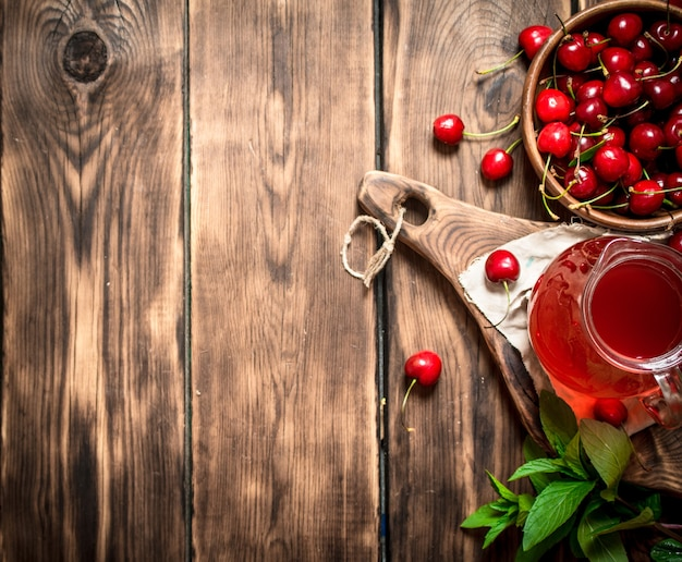 Свежий вишневый сок. на деревянном фоне.