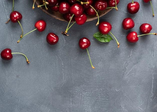 검은 슬레이트 테이블에 있는 신선한 체리 회색 배경의 물방울에 익은 달콤한 딸기