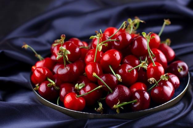 Свежая вишня на темной шелковой ткани. спелые сладкие ягоды в капельках воды