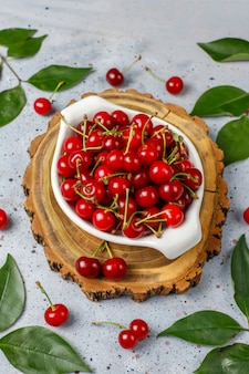 Fresh cherry on plate on grey table top view
