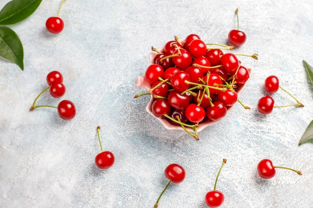 Fresh cherry on plate on grey table