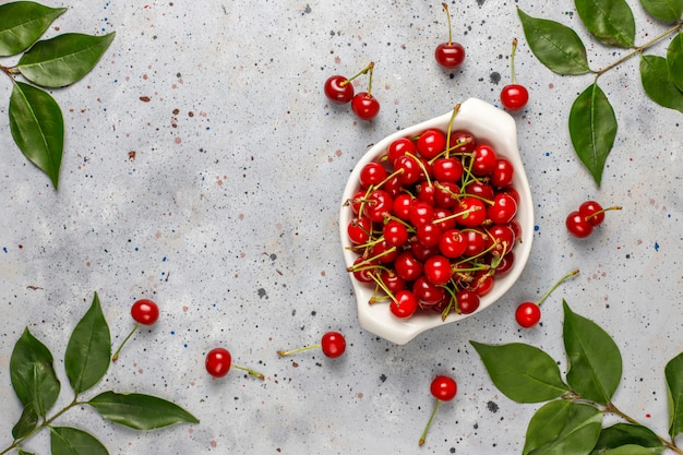 Fresh cherry on plate on grey table.