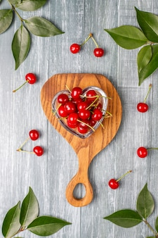 Fresh cherry on plate on wood table