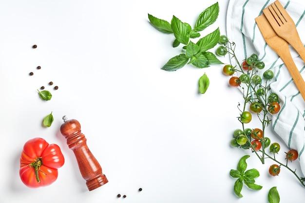 흰색 배경에 신선한 체리 토마토 가지, 바질 잎, 냅킨, 후추, 후추 밀. 음식 요리 배경과 조롱.