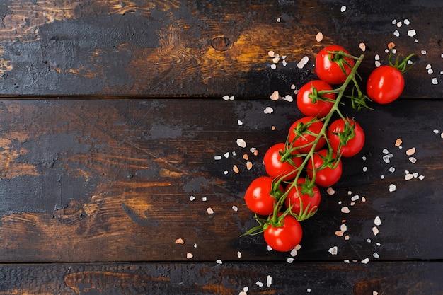 古い木製の背景に新鮮なチェリー トマト、バジルの葉、モッツァレラチーズ、オリーブ オイル。カプレーゼサラダの具材。選択と集中。
