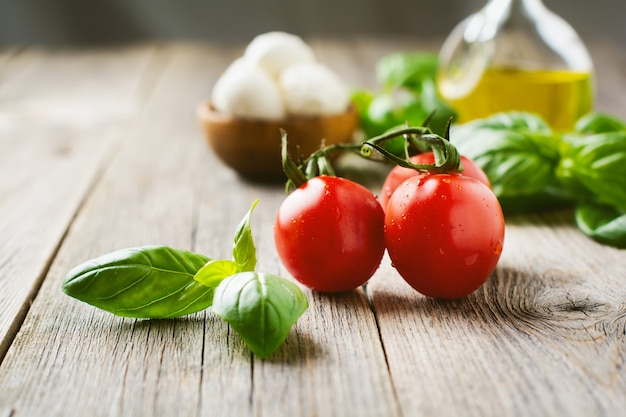 古い木製の背景に新鮮なチェリートマト、バジルの葉、モッツァレラチーズ、オリーブオイル