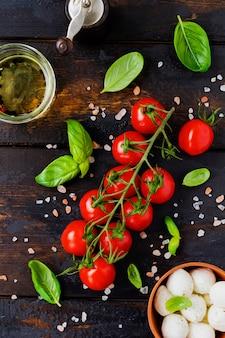 古い木の表面に新鮮なチェリー トマト、バジルの葉、モッツァレラチーズ、オリーブ オイル。カプレーゼサラダの具材。選択と集中。