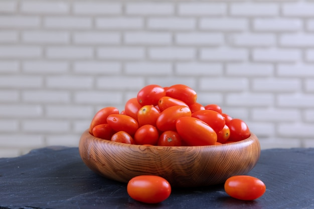 Fresh cherry tomatoes on bowl wooden with white wall.