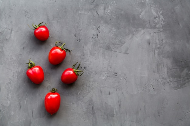 Fresh cherry tomatoes on a gray concrete background