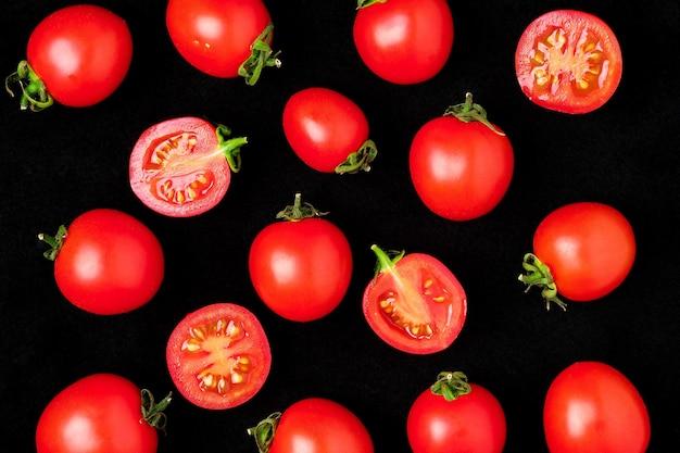 Свежие помидоры черри изолировать на черном целиком и разрезать пополам.