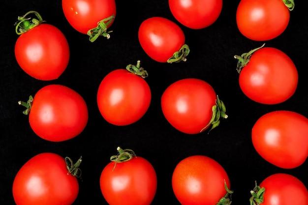Свежие помидоры черри, изолированные на черном. Premium Фотографии