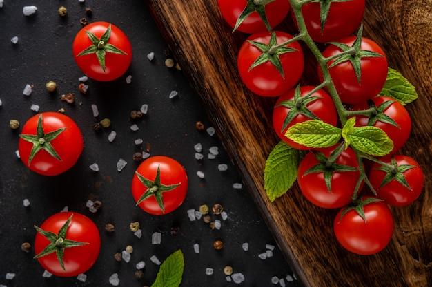 Свежие помидоры черри на черном фоне со специями.