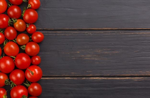 木製の黒い背景に新鮮なトマト。上面図